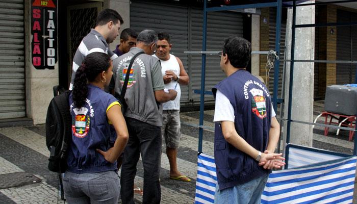 Fiscais verificam os documentos do ambulante legalizado em Alcântara. Foto: Julio Diniz / Ascom - Prefeitura.