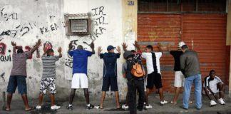 Policiais revistam pessoas na comunidade Nova Holanda, complexo da Maré.