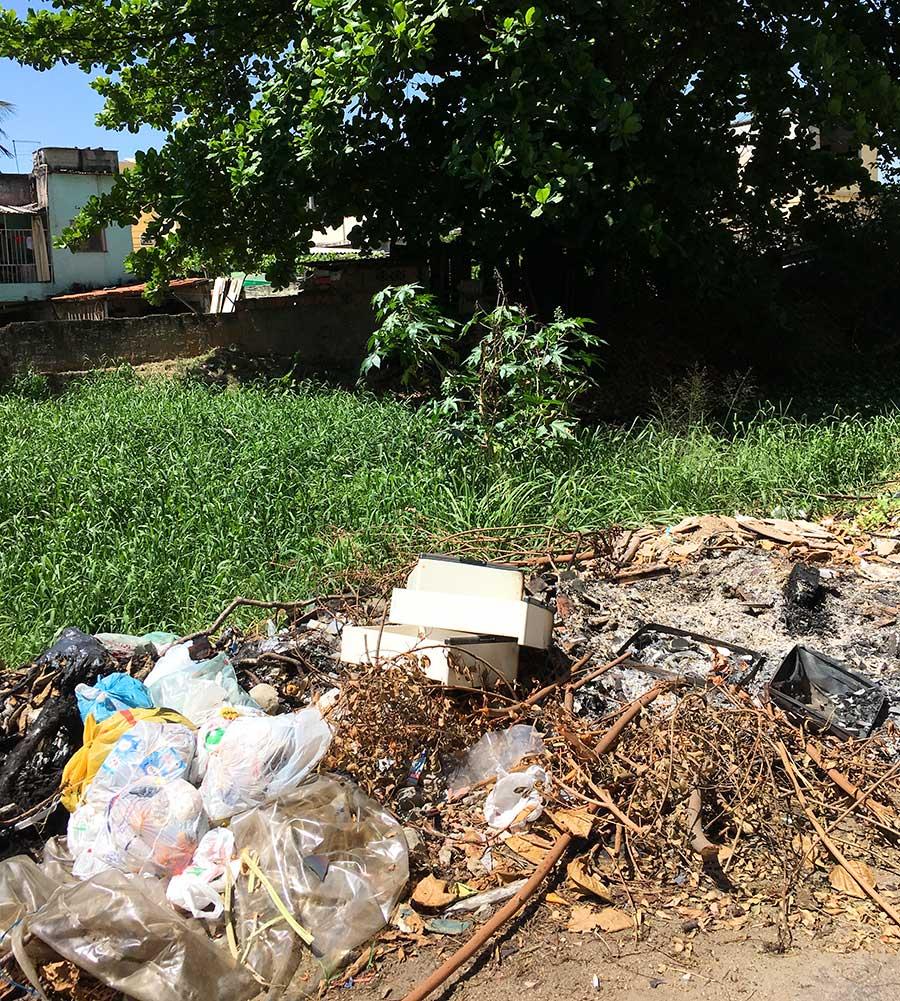 """Lixo jogado e """"armazenado"""" na margem do rio no Porto Novo – São Gonçalo. Não satisfeitos em deixa o lixo ali, insistem em queimá-lo também. Foto: Sim São Gonçalo"""