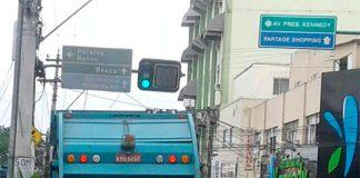 Pessoas remexendo o lixo dentro do caminhão coletor no Centro de São Gonçalo